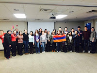 a large group of students are standing in front of a presentation screen. one is holding the armenian flag