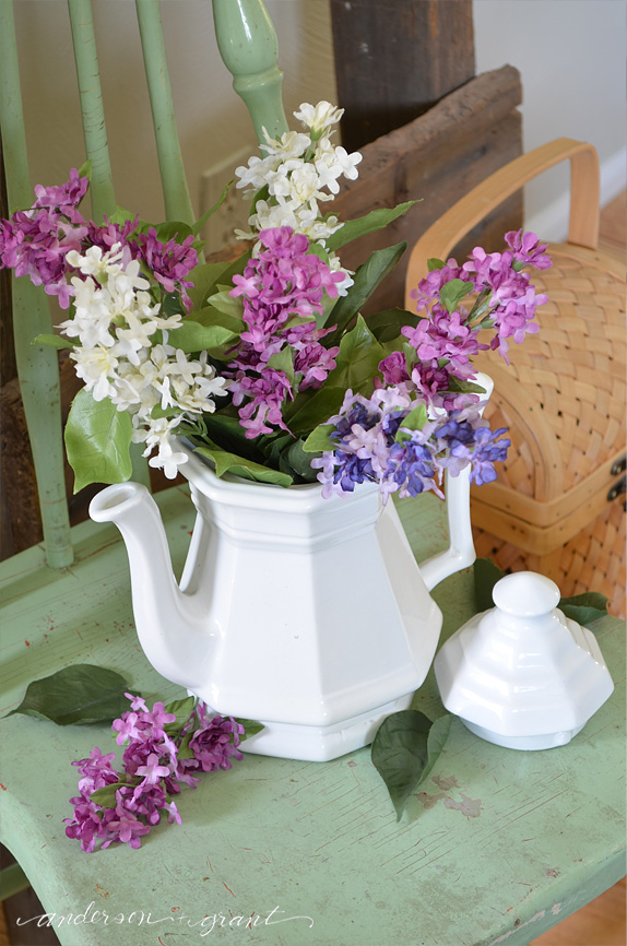 Filling a white ironstone teapot with lilacs in spring | anderson + grant