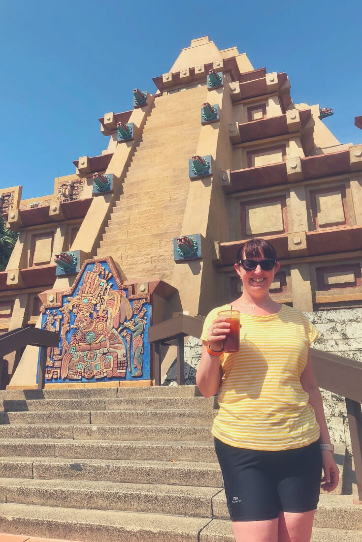 Morgan Prince holding a flavoured tequila drink while standing in front of Mexico, in Epcot, Walt Disney World