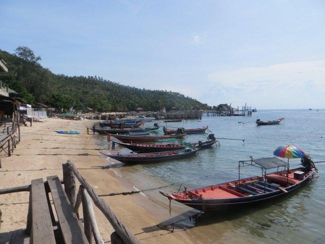 Лодки на пляже рядом с пирсом