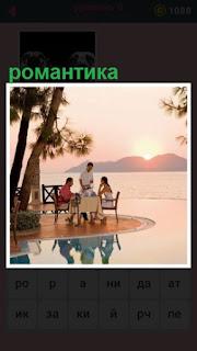 за стоиком сидят двое, у которых романтический ужин на берегу