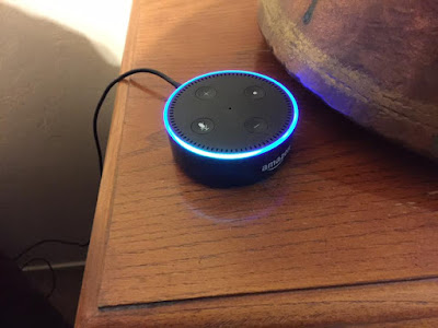 my amazon echo dot on side table,  top blue ring light is illuminated showing that Alexa is working on a question.