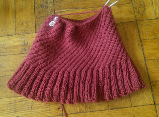 A worsted-weight hat knit in red yarn with spiralling cables and a flared ribbed brim.