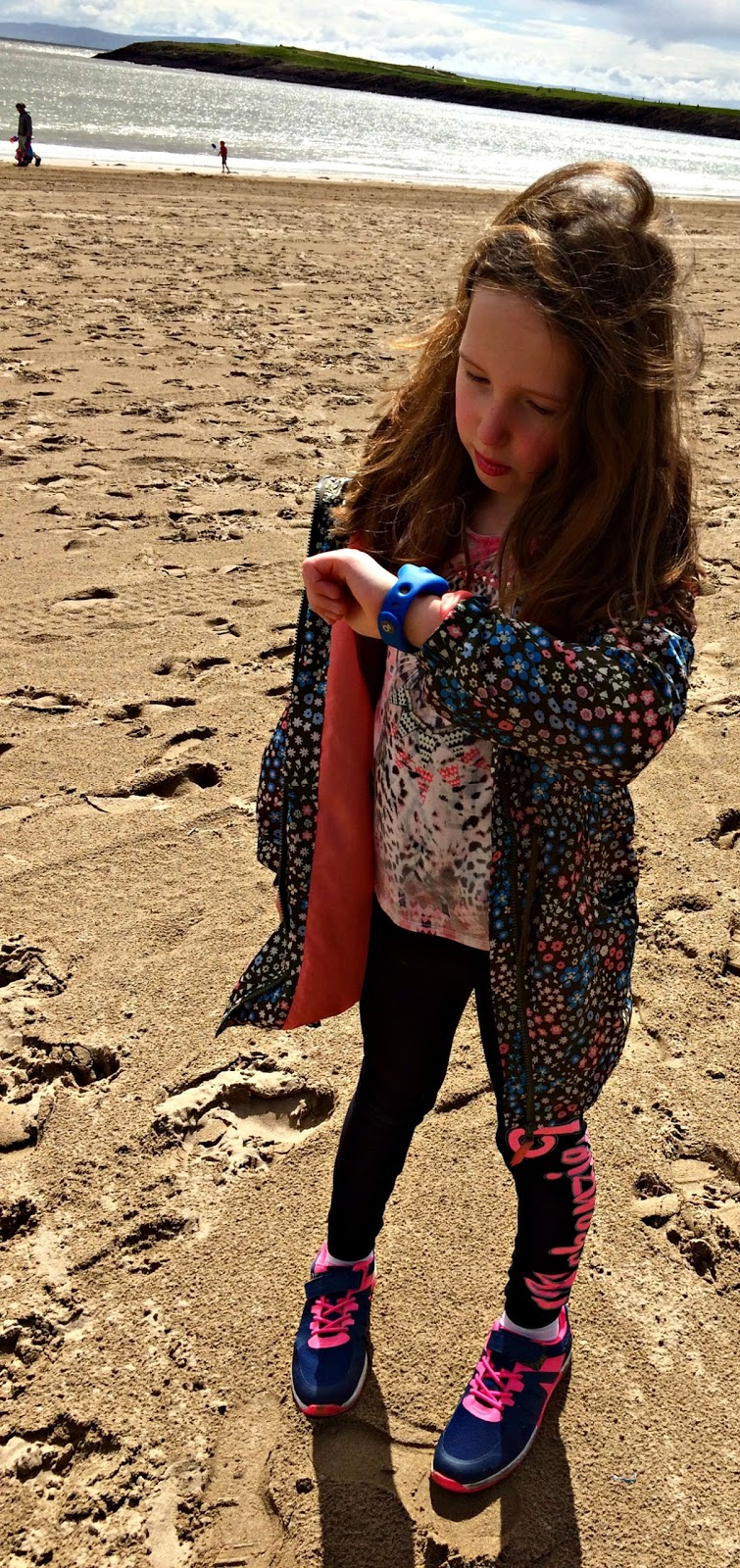 Caitlin looking at the dokiWatch on Barry Island Beach