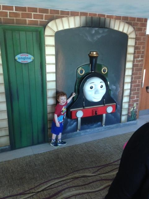 Little boy standing next to a train wall feature
