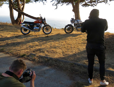 Two photographers take photos of two motorcycles on a cliff top.