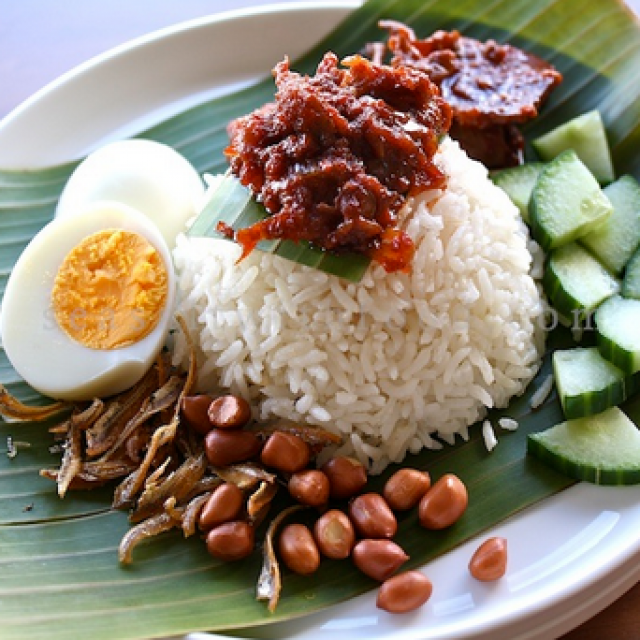 The dish is described as rice 'soaked and cooked in coconut milk' and 'garnished with anchovies, cucumbers, roasted peanuts, hard-boiled egg and spicy sambal sauce'.
