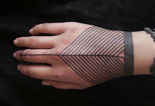Linhas de atender a um quarenta e cinco graus de ângulo no centro do utente mão no preto tatuagem.