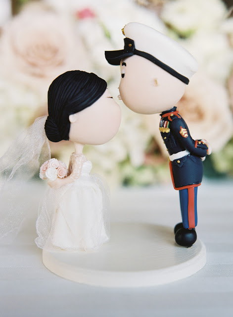 A tiny sailor figurine kisses his bride atop the wedding cake