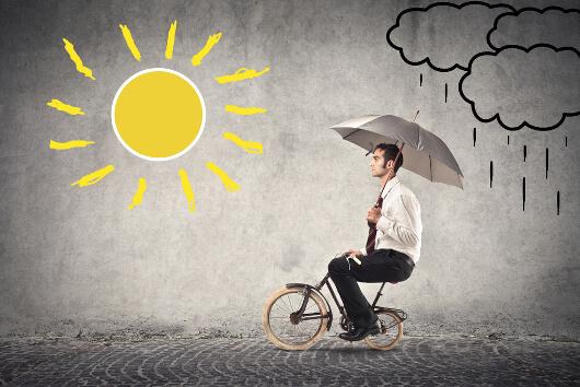 Hombre en bicicleta pequeña con una sombrilla
