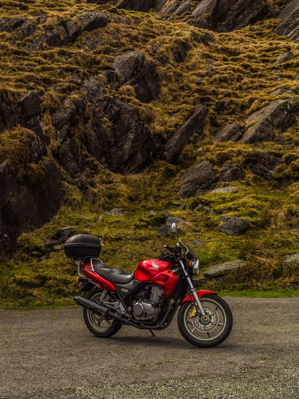 A red Honda CB500 pictured under a rocky and mossy mountain on the Healy Pass in Ireland.