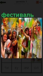Веселые девушки и ребята разукрашенные краской на фестивале с телефонами делают селфи