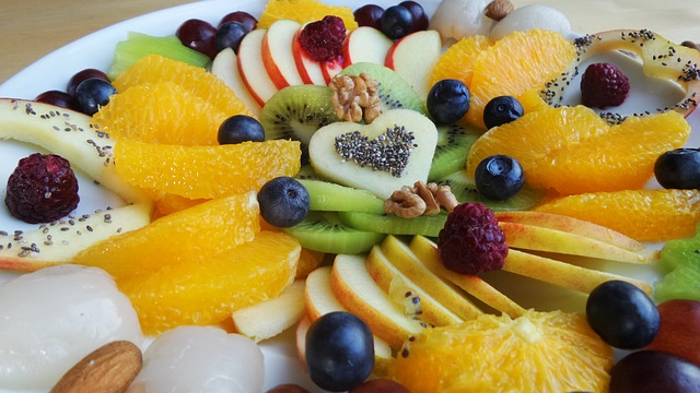 Platter of summer fruits: oranges, apples, blueberries, raspberries, walnuts