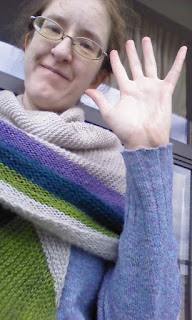 A woman smiling at the camera, waving her hand. There's a shawl wrapped around her shoulders, neck and chest. The shawl is cream with 5 colour stripes, the stripes are a gradient from purple to green.