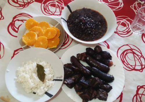 Platos por separado de carne y embutidos, naranja, arroz y frijoles
