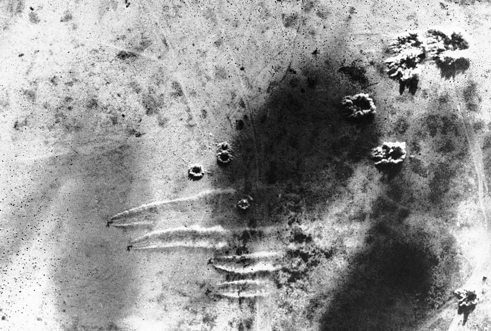 This view of an air raid on an Axis plane base at Martuba, near Derna, in Libya on July 6, 1942 was made from one of the South African planes which took part in the raid. The four sets of white streaks in the lower half show the dust of Axis planes speeding along the ground to escape as bomb bursts appear near them and in upper center.