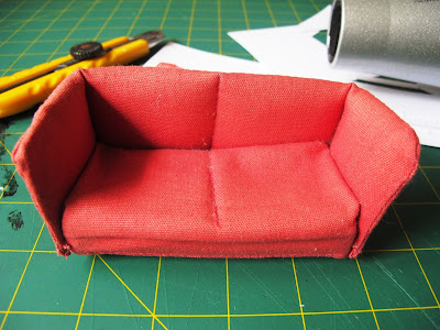 Lundby dolls' house sofa sitting on a workbench with tools in the background.