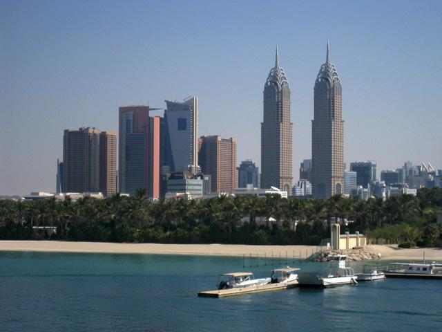 Una playa virgen en Dubai, a la sombra de árboles y rascacielos