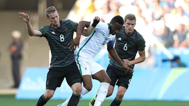 Mikel challenging for the ball with two German players