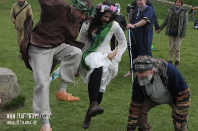 This image shows a handfasted couple 'jumping the besom' at a traditional pagan handfasting