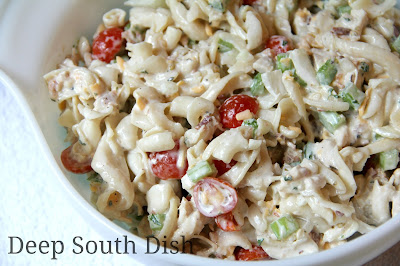 Chicken Pasta Salad made with a homemade Ranch style vinegar dressing, short cut pasta, cooked chicken, Vidalia onion, celery, cheese, bacon, peas and tomatoes.