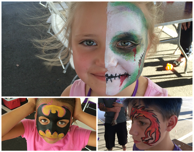 A few young kids with their faces painted like Zombies, Batman, and a Dragon