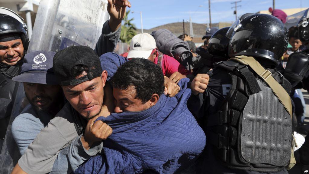 Migrantes centroamericanos chocan con la policía mexicana en el cruce fronterizo de Chaparral en Tijuana / AP