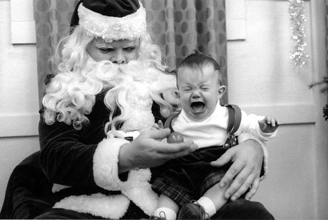 A baby cries on Santa's lap while Santa offers him a ball. A Pleasant Christmas Story and other stories of Christmas Creepers. marchmatron.com.jpg