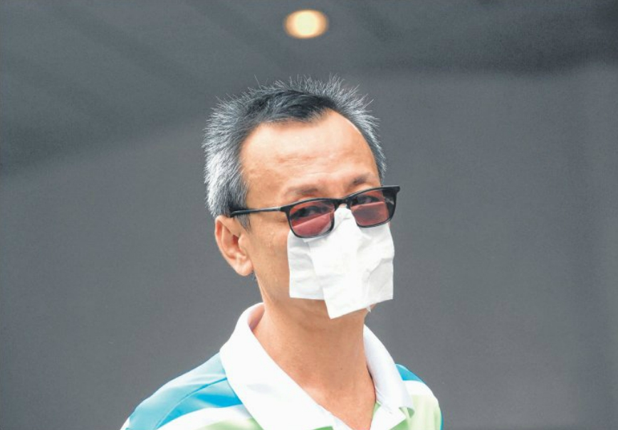 Undercover: A man fashions a 'face mask' with tissue as the haze worsened here yesterday