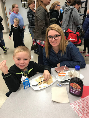 A woman sitting at a table, in a cafeteria next to a child who is finishing eating his breakfast