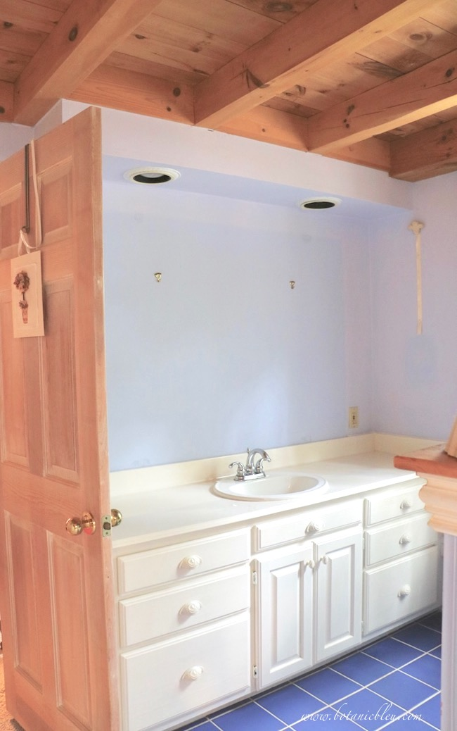 white vanity in master bathroom with blue ceramic tile, post and beam ceiling, before new blue wall paint