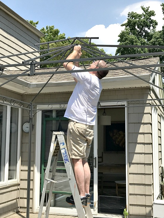 Man on ladder gazebo assembly