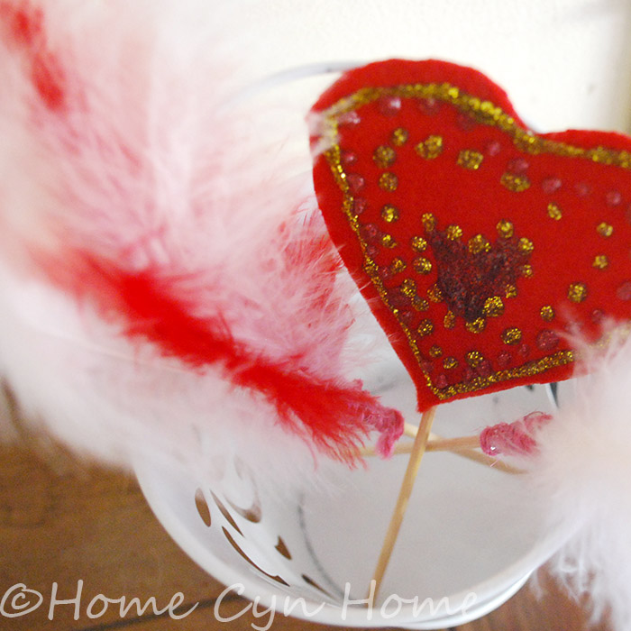 Felt hearts and feather in small tin buckets makes for an adorable Valentine's day decor idea