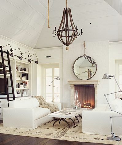 living room with dueling sofas, a marble top coffee table separating them, a fireplace with a round mirror on the mantel, metal chandelier, built in bookcase and cabinets with a sliding ladder to reach higher shelves