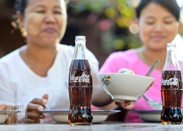Two women enjoy food and bottles of Coke during the filming of the dinner scene for Coca-Cola Myanmar.
