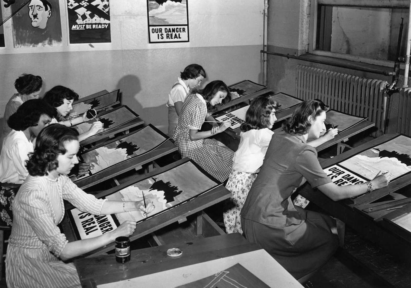 The art assembly line of female students busily engaged in copying World War II propaganda posters in Port Washington, New York, on July 8, 1942. The master poster is hanging in the background.