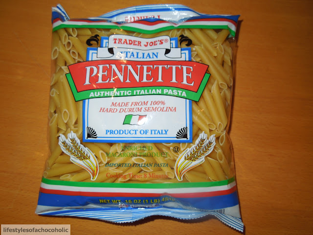 penne pasta in bag from trader joes on a wood background