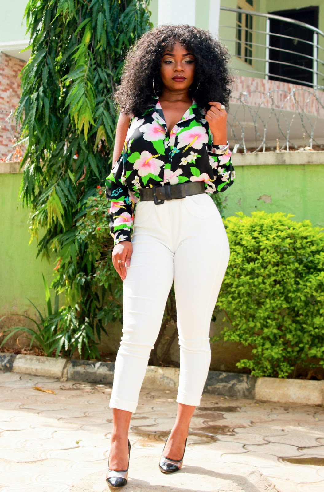 Floral print shirt with white pants and black court shoes