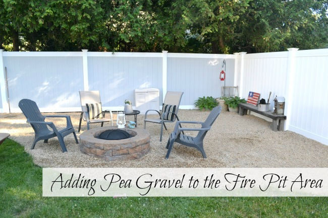 Vinyl fenced area with fire pit and plastic chairs
