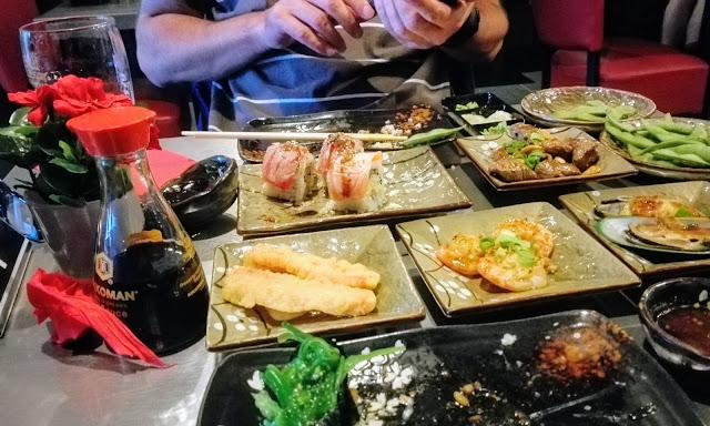 Uitgebreide tafel met hapjes tijdens All you can eat sushi.