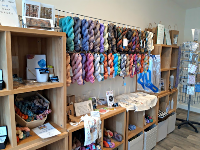 Photo of display shelves containing gifts and yarn, and wall racks for hand-dyed yarn