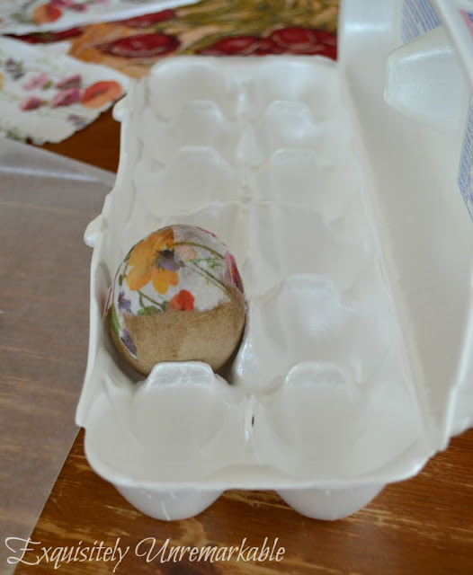 A decoupaged egg in an egg carton