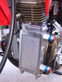 XR100モタードのオイルクーラーコアガードはプロト製。フロントタイヤが小石を跳ね上げてオイルクーラー本体の破損を防ぐ為に付けています。あと武川からオプションで販売されているサーモスタットを取付ければオーバークールの心配から解放されます。