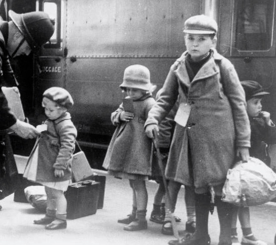 Photograph of a policeman helping young evacuees as they prepare to leave a London station for a train ride to their temporary homes. Part of the Civilian Evacuation Scheme in Britain during the Second World War. Images from Wikimedia Commons
