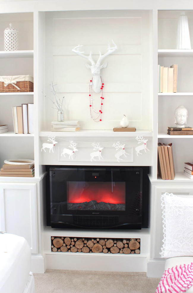 white stag on mantel with pom pom garland and little paper deer garland