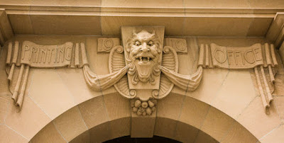 Why is there a 'Printer's Devil' over the main entrance of the Printing Office, George Street, Brisbane?.