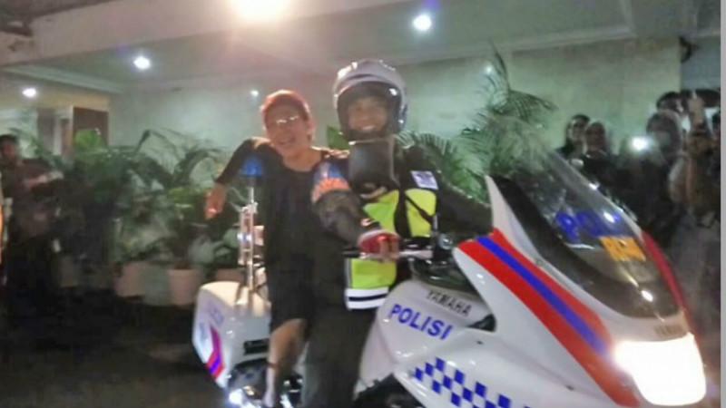Menteri Kelautan dan Perikanan Susi Pudjiastuti menaiki motor polisi pengawalnya
