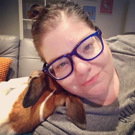image of me from the shoulders up, lying sideways on my sofa; I have my hair pulled back and I'm wearing my blue-framed glasses and a grey Philadelphia Union t-shirt; Dudley's head is resting on my shoulder