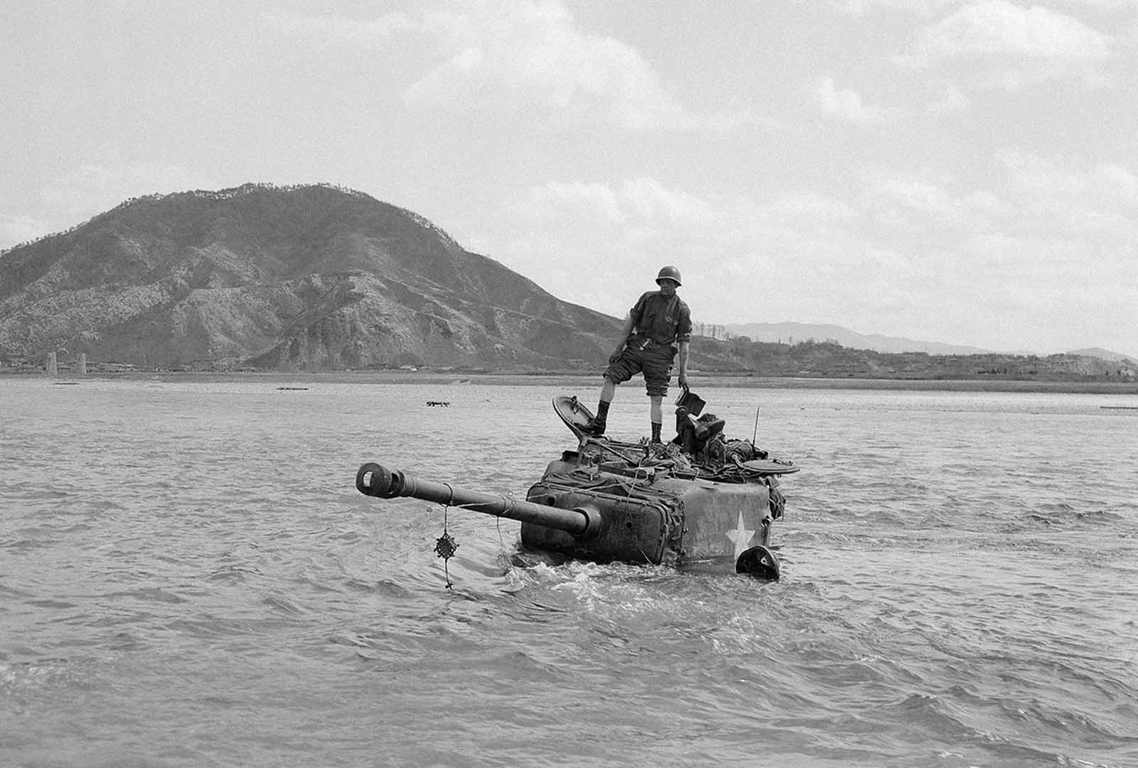 Crew members stand on top of their tank after they got stranded in river bed dip as they attempted to find a shallow crossing in the swollen Pukhan river. The tank was later towed out to safety by a tank retriever, April 7, 1951 in Korea.