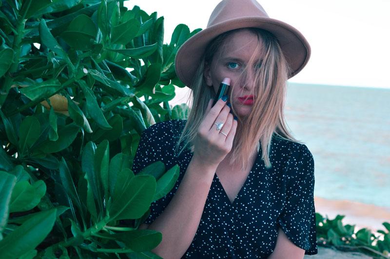 beach beauty tips apply strobing boho girl in hat on beach